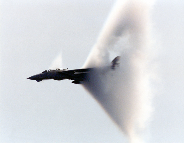 """A F-14 Tomcat from Fighter Squadron Thirty-Two (VF-32), """"Swordsmen"""", breaks the sound barrier during COMTUEX, Comprehensive Training Unit Exercise, while stationed on board USS Harry S. Truman (CVN 75). COMTUEX is designed to bring the aircraft carrier/carrier air wing team together as a cohesive fighting unit while giving the team """"blue water"""" certification for operating at sea"""