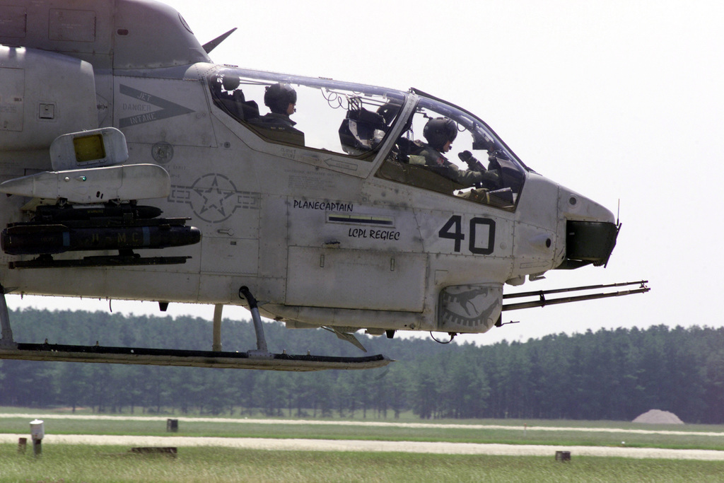 A United States Marine Corps AH-1W Super Cobra attack helicopter hovers above the Shaw Air Force Base, South Carolina, flight line as it positions itself in a hot pit refueling area. The AH-1W is assigned to the Marine Corps Air Station New River, North Carolina. USMC CH-46E Sea Knights and AH-1W's are being hot pit refueled by a USMC KC-130 of Marine Aerial Refueling/Transport Squadron Two Five Two (VMGR-252) from MCAS Cherry Point, NC. The hot pit refueling, where one or more aircraft refuel with their engines running, occured as the helicopters transited the area while deploying to Naval Air Station Atlanta, Georgia for an exercise, 14 August 2000