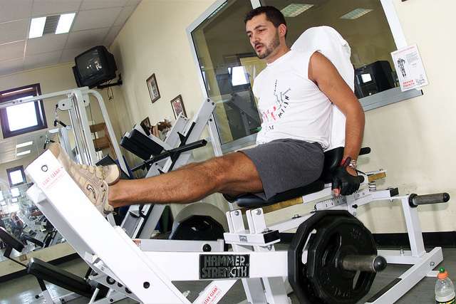 Left side front view medium shot as M2 Nevio Della Sala, Italian military member at Ghedi Air Base, Italy uses the leg press. The Services Flight at Ghedi takes care of the gym and keeps it open for Americans and Italians to workout during the day