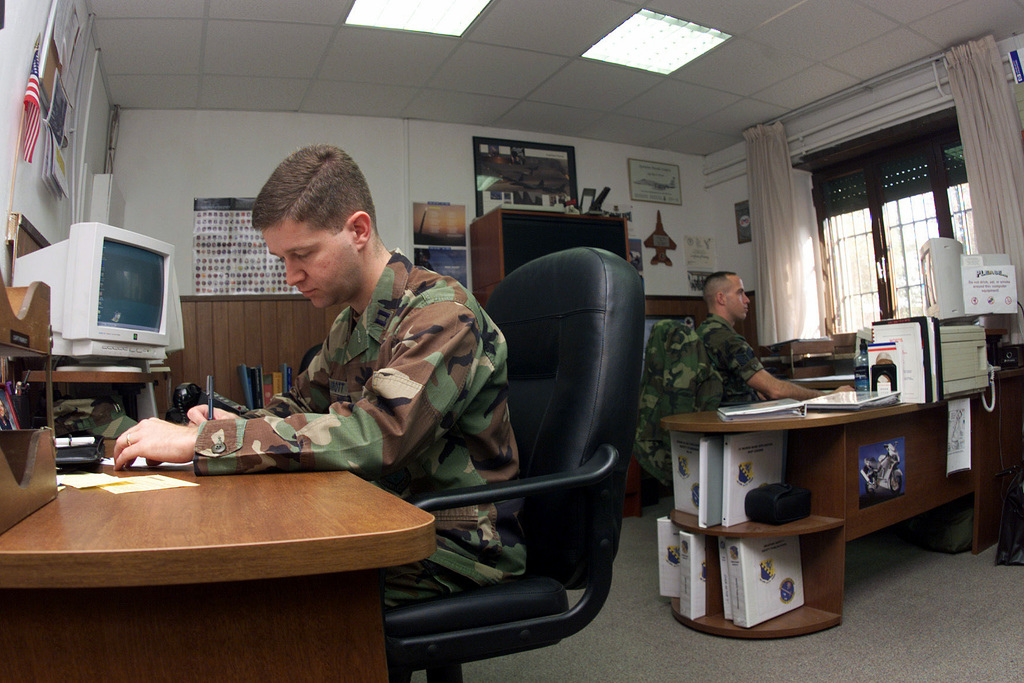 Left side profile medium shot as US Air Force Captain Mark Parrott (left) and Technical Sergeant Roy Person, 831st Munitions Support Squadron Ghedi Air Base, Italy, prepare for the upcoming 31st Fighter Wing Functional STAFF visit. CAPT Parrot and TSGT Person are part of the Readiness/Safety Section who ensure the Squadron remains inspection ready and compliant with all Operating Instructions