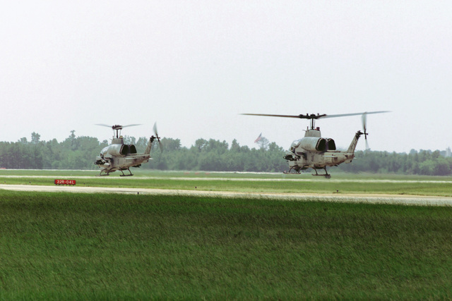 Two United States Marine Corps AH-1W Super Cobra attack helicopters hover above the Shaw Air Force Base, South Carolina flight line as they await permission to take-off. The AH-1W's are assigned to Marine Corps Air Station New River, North Carolina. United States Marine Corps CH-46E Sea Knights and AH-1Ws were hot pit refueled by a USMC KC-130 of Marine Aerial Refueling/Transport Squadron Two Five Two (VMGR-252) from MCAS Cherry Point, NC. The hot pit refueling, where one or more aircraft refuel with their engines running, occured as the helicopters transited the area while deploying to Naval Air Station Atlanta, Georgia, for an exercise, 14 August 2000