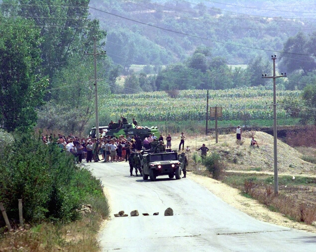 United States Army and Russian soldiers of the Kosovo Froce (KFOR) try to disperse an angry Serbian mob near the town of Domorovce, Kosovo. After two Serbian men disappeared, the Serbians believe the Albanians abducted the men and began to make threats and road obstructions to stop the Albanians from traveling safely through town. The Albanians began to form a mob to confront the Serbians until USA and Russian KFOR troops made a wall between the opposing sides. Vehicles include M998 High-Mobility Multipurpose Wheeled Vehicle (HMMWV). Task Force Falcon, Operation Joint Guardian, 15 August 2000