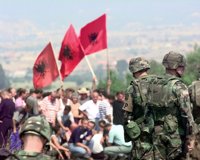 United States Army soldiers watch as an angry Albanian mob, wave Albanian National Flags and prepare to march to the town of Domorovce, Kosovo. The soldiers are members of the 108th Military Police Company (MP), 503rd MP Battalion, Fort Bragg, North Carolina. After two Serbian men disappeared, the Serbians believe the Albanians abducted the men and began to make threats and road obstructions to stop the Albanians from traveling safely through town. The Albanians began to form a mob to confront the Serbians until US and Russian Kosovo Force (KFOR) troops made a wall between the opposing sides. Task Force Falcon, Operation Joint Guardian 14 August 2000