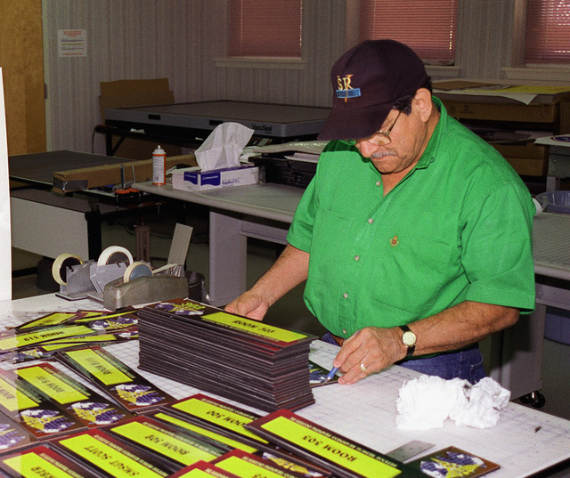 Department of the Army Civilian Frank Barron prepares custom placards for specialized Identification in the Fort Sam Houston Audio/Visual production Facility, Fort Sam Houston, San Antonio, Texas
