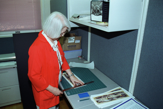 Department of the Army Civilian, Ms Geraldine Clayton trims design identification placards at the Fort Sam Houston Audio/Visual Production Facility, Fort Sam Houston, San Antonio, Texas