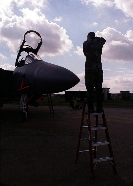 AIRMAN First Class James L. Harper Jr., a photographer from the 48th Communications Squadron, 48th Fighter Wing, Royal Air Force Base Lakenheath, United Kingdom, takes photographs of an F-15 Strike Eagle aircraft for wing mission documentation