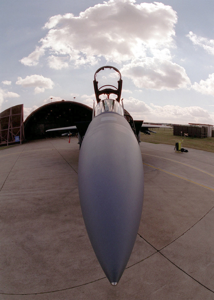 Close up, front view, camera looking over the top of an F-15E Strike Eagle radome, aircraft canopy is open, hangar, blue sky and clouds in background. Aircraft is assigned to the 492nd Fighter Squadron, 48th Fighter Wing, Royal Air Force Lakenheath, United Kingdom. The Air Force F-15 Strike Eagle is a tactical fighter equipped with a mixture of maneuverability, range, weapons, acceleration, and avionics which enables the F-15 to be the superior fighter of air to air combat. (Duplicate image, see also DF-SD-01-06162 or search 000816-F-4177H-003)
