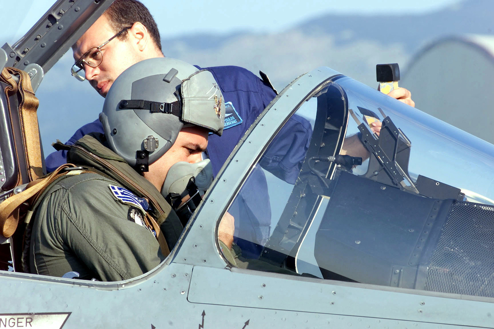 Left side profile medium close-up shot as Greek Air Force STAFF Sergeant John Papadopoulos (background), an aircraft mechanic of the Hellenic (Greek) Air Force, 114th Composite Group, 331st Tactical Fighter Wing, Greece, assist Captain Stefanos Ampouleris strap into his Mirage 2000 Fighter. The Hellenic unit is at Aviano Air Base, to train with the 510th Fighter Squadron. The Mirages provide valuable dissimilar training allowing 510th Fighter pilots the opportunity to train against other types of aircraft. (Duplicate image, see also DF-SD-01-06167 or search 000816-F-4728F-003)