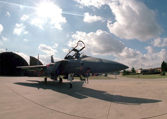 Medium shot, right front view, F-15E Strike Eagle, red safety flags on aircraft, parked on flight line, sun, white clouds and blue sky in background. Aircraft is assigned to the 492nd Fighter Squadron, 48th Fighter Wing, Royal Air Force Lakenheath, United Kingdom. The Air Force F-15 Strike Eagle is a tactical fighter equipped with a mixture of maneuverability, range, weapons, acceleration, and avionics which enables the F-15 to be the superior fighter of air to air combat. (Duplicate image, see also DF-SD-01-06160 or search 000816-F-4177H-001)