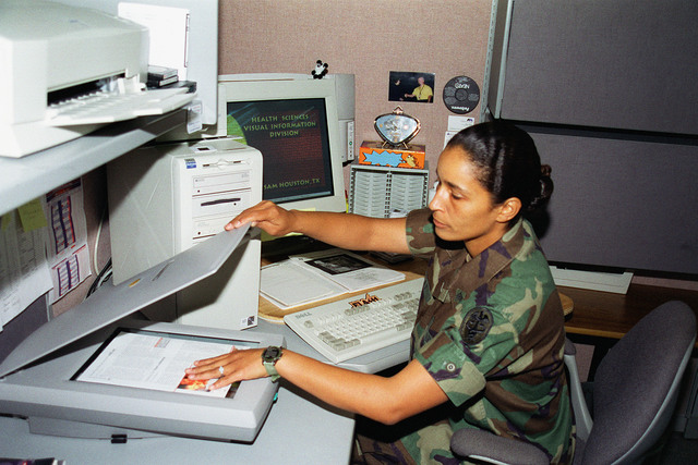 US Army Sergeant Danielle Holliday scans pages to be used in a presentation for a Health Sciences Visual Information briefing. SGT Holliday works in the Fort Sam Houston Audio/Visual Production Facility, Fort Sam Houston, San Antonio, Texas