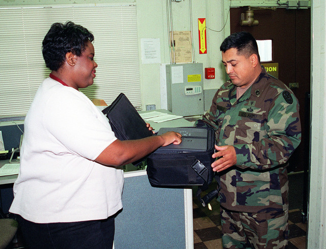 Department of the Army civilian Liz Clay, of the Fort Sam Houston Audio/Visual Production Facility, signs out a laptop computer to a Soldier, on Fort Sam Houston, San Antonio, Texas