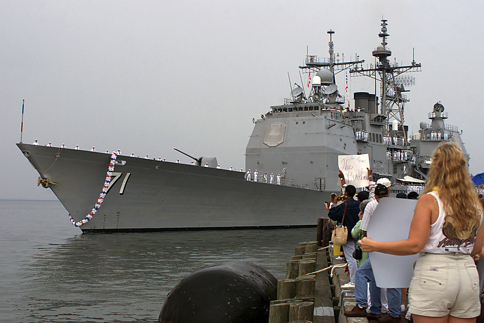 Spectators watch and wait for the arrival of friends and family members aboard the USS CAPE ST. GEORGE (CG 71), at a pier on Naval Station Norfolk, Virginia