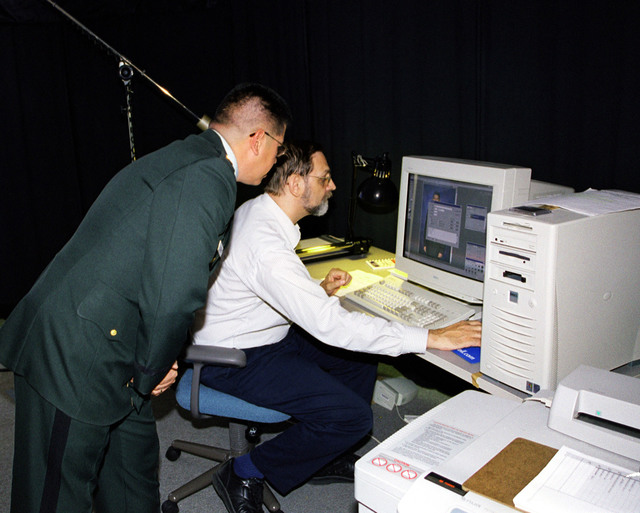 Department of the Army civilian Donald Beardslee (Seated) checks out information for accuracy before printing a Department of the Army (DA) photo at the Fort Sam Houston Audio/Visual Production Facility, Fort Sam Houston, San Antonio, Texas