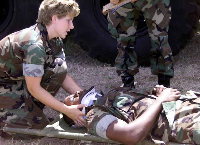 US Navy Hospital Corpsman 3rd Class E. Smith, of the Combat Service Support Group-3 checks the injuries of a mock neck injury victim during the August 24th, 2000 MEDEVAC (Medical Evacuation) mass casualty drill aboard Marine Corps Base (MCBH), Kaneohe Bay, Hawaii