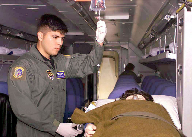 US Air Force Aerovac Technician, SENIOR AIRMAN Elco Lozano Jr., 86th Aeromedical Evacuation Squadron, Ramstein Air Base, Germany, checks on an IV bag for a simulated patient for an Air Show in Gothenburg, Sweden, on August 26th, 2000. (Duplicate image, see also DF-SD-01-06188 or search 000826-F-6470D-504)