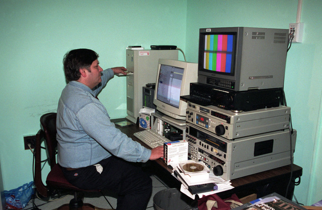 Mr. Gary French, a technician with the US Army Visual Information Center, loads a compact disk into his computer, while working at his multimedia workstation, inside the Electronic Imaging Graphic Service Divison