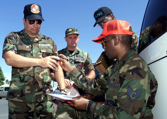 MASTER Sergeant James Deandrade (left), 40th Flight Test Squadron, Eglin Air Force Base, Florida, receives keys from STAFF Sergeant Young during a Joint Expeditionary Force Experiment at Nellis Air Force Base, Nevada