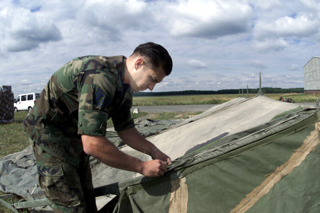 US Air Force STAFF Sergeant Darrell McDonald, 31st Civil Engineer Squadron, 31st Fighter Wing, Aviano Air Base, Italy, cinches down the outer weather covering for a communications tent. The Civil Engineer team is one of several that are getting assets in place in support of Exercise IRON CLAW, at Kuchyna Air Base, Slovakia. The exercise will allow the 510th Fighter Squadron (not shown) to test a new scoring system on the bombing range. About 250 Air Force personnel from Aviano Air Base, Italy, are participating in the exercise