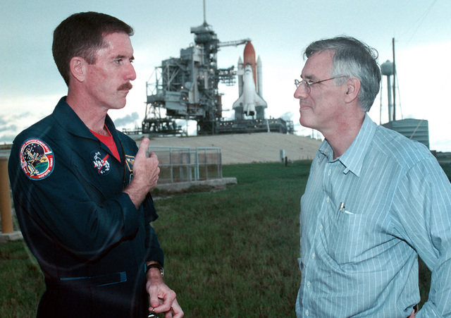 US Navy (USN) ENSIGN (ESN) Jim Reilly (left), an Astronaut with the National Aeronautics and Space Administration (NASA), speaks with The Honorable Richard Danzig, Secretary of the Navy, at the launch pad of the space shuttle Atlantis at Cape Canaveral, Florida (FL)