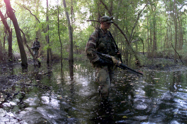 US Air Force SENIOR AIRMAN Brian Morrill, 1ST Security Forces Squadron (SFS) junior patrolman, and M-60 gunner for the 1ST SFS Contending Warrior team, braves a mosquito and tick-infested forest during tactical training at Langley Air Force Base, Virginia. The Langley Contending Warrior team has been preparing for months for a competition that takes place in the Nevada desert
