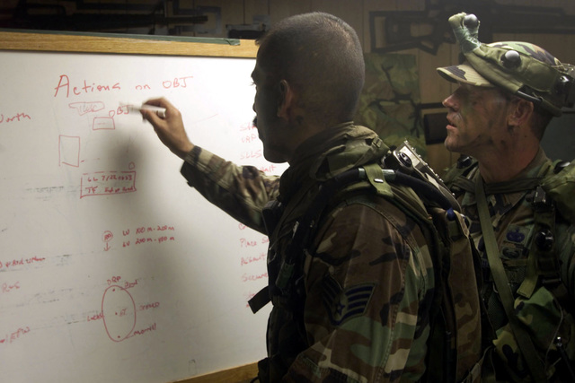 US Air Force STAFF Sergeant Alfred Orozco, foreground, 1ST Security Forces Squadron (SFS) dog handler and assistant team leader, and US Air Force 2nd Lieutenant Keith McCormack, 1ST SFS assistant operations officer and team leader for the 1ST SFS Contending Warrior team, plot strategies prior to making a hostage rescue attempt during tactical training at Langley Air Force Base, Virginia. The Langley Contending Warrior team has been preparing for months for a competition that takes place in the Nevada desert