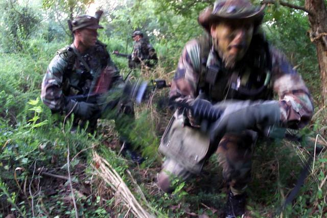 US Air Force STAFF Sergeant Alfred Orozco, foreground, 1ST Security Forces Squadron (SFS) dog handler and assistant team leader, and US Air Force 2nd Lieutenant Keith McCormack, 1ST SFS assistant operations officer and team leader for the 1ST SFS Contending Warrior team, approach an enemy forces camp (not shown) prior making a hostage rescue attempt during tactical training at Langley Air Force Base, Virginia. The Langley Contending Warrior team has been preparing for months for a competition that takes place in the Nevada desert