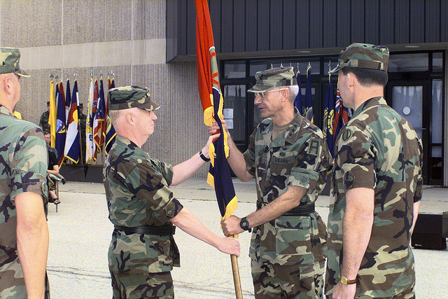 Lieutenant General John M. Riggs passes the 85th Division unit colors to Colonel Steven P. Best while Brigadier General Ronalds Mangum looks on