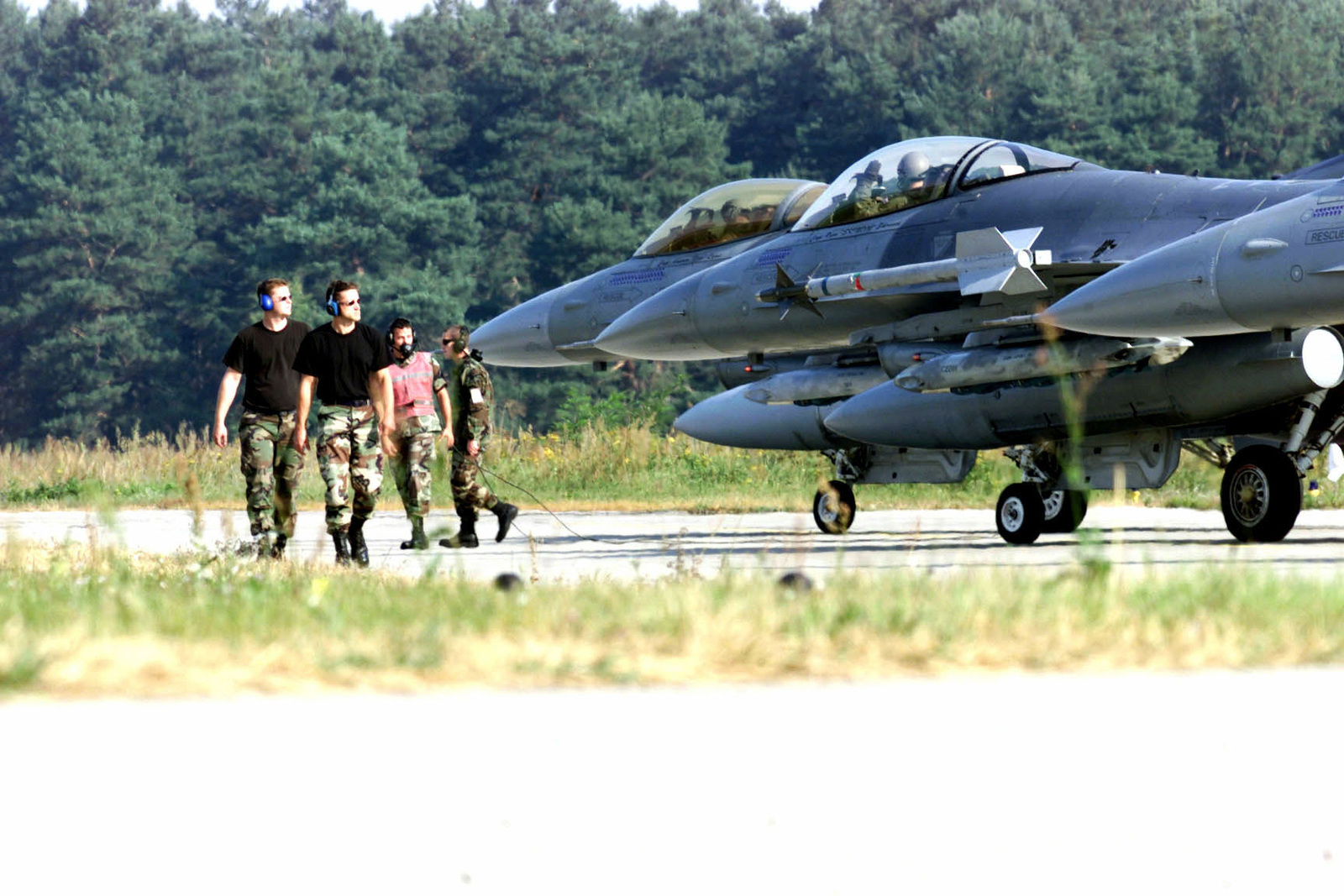 United States Air Force personnel, 510th Fighter Squadron, 31st Fighter Wing, deployed from Aviano Air Base, Italy, walk the line as they prepare to arm the next F-16C Fighting Falcon before it is launched for the day's first sortie. Training Exercise Iron Claw, Kuchyna AB, Slovakia, 11 September 2000