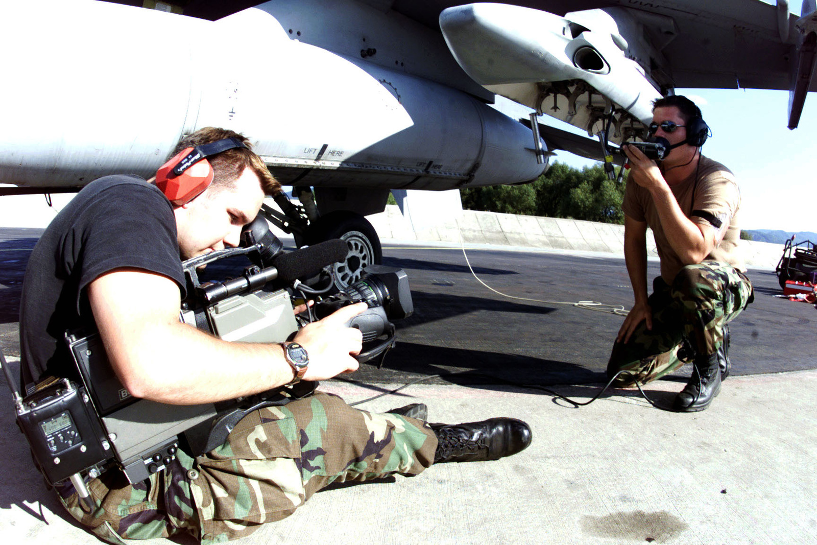 United States Air Force SENIOR AIRMAN Noah Park, a radio and television broadcaster, Det 8, Aviano Air Base, Italy, documents SRA Ed Neely, USAF, Armament Systems journeyman, 510th Fighter Squadron, 31st Fighter Wing, deployed from Aviano AB, performing an operational check of a SUU-22 (Suspended Underwing Unit) weapons pylon at Kuchyna AB, Slovakia. Training Exercise Iron Claw, 12 September 2000