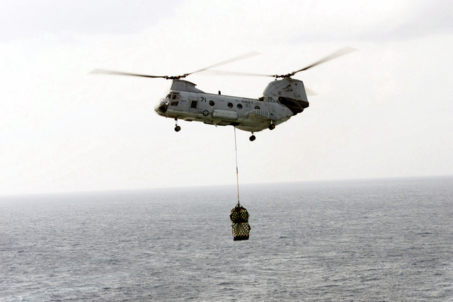 A CH-46E Sea Knight from HC-11 Detachment 5 approaches with supplies dangling in a suspension cradle, during a Vertical Replenishment (VERTREP) of the USS TARAWA (LHA-1) in the Western Pacific