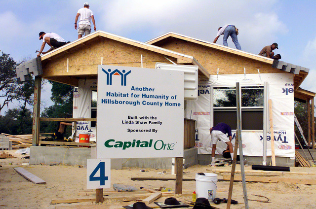 Several people apply roof shingles to a house at Grant Park. Members from MacDill Air Force Base participated in the Habitat For Humanity Worldwide 1 week- 10,000 houses- Mission Possible Home Building Project