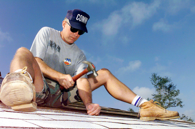US Air Force CHIEF MASTER Sergeant Jeff Lawerence, 6th Communications Squadron, MacDill Air Force Base, Flordia, applies roof shingles to a house at Grant Park. Members from MacDill AFB, participated in the Habitat For Humanity Worldwide 1 week- 10,000 houses- Mission Possible Home Building Project