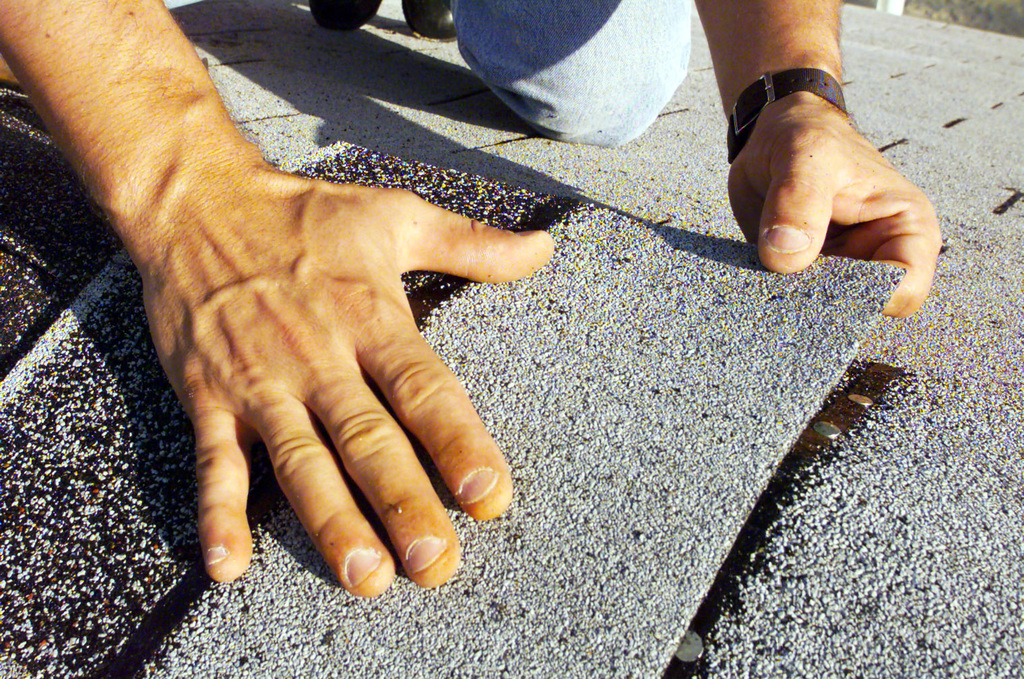 Close up of hands applying roof shingles to a house at Grant Park. Members from MacDill Air Force Base, Florida, participated in the Habitat For Humanity worldwide 1 week- 10,000 houses- mission possible home building project