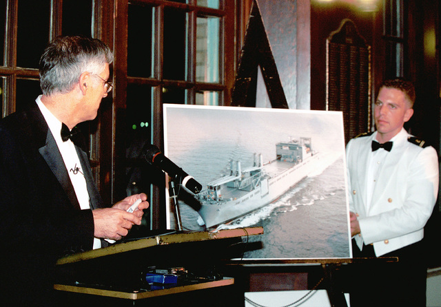 Secretary of the Navy Richard Danzig unveils a drawing of the new United States Navy ship USS Benavidis, as Midshipmen Second Class Ricky, looks on at the United States Naval Academy, at Annapolis, Maryland