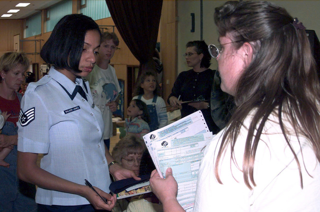US Air Force STAFF Sergeant Kelli Jones (Left), of the USAFE Regional Supply Squadron, Sembach Air Base, Germany, gets information from Ms Desy Maus about Sembach's Girl Scouts during the Sembach Community Information Fair. The fair was conducted Thursday September 14th, 2000, from 1800-2000 hours at the Middle School Community Center. Continuing for a second year in a row, it was an opportunity for service members and their families to meet and talk to representatives from different agencies providing services to Sembach AB. The agencies at the fair not only provided to its guest useful information, but also free food and drinks as well as games for kids and some door prizes were handed out