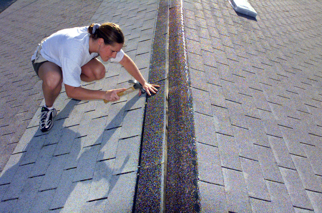 US Air Force STAFF Sergeant Lorraine Detaeye-Osgood, 6th Communications Squadron, MacDill Air Force Base, Florida, applies roof shingles to a house at Grant Park. Members from MacDill AFB participated in the Habitat For Humanity worldwide 1 week- 10,000 houses- mission possible home building project