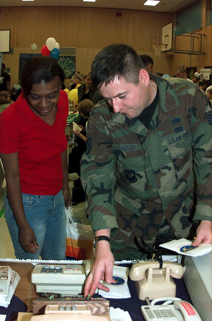 US Air Force STAFF Sergeant Paul Healey (Right) of the 886th Communications Squadron, Sembach Air Base, Germany, informs a community member about telephone services on base during the Sembach Community Information Fair. It was conducted Thursday, September 14th, 2000, from 1800-2000 hours at the Middle School Community Center. Continuing for a second year in a row, it was an opportunity for service members and their families to meet and talk to representatives from different agencies providing services to Sembach AB. The agencies at the fair not only provided to its guest useful information, but also free food and drinks as well as games for kids and some door prizes were handed out