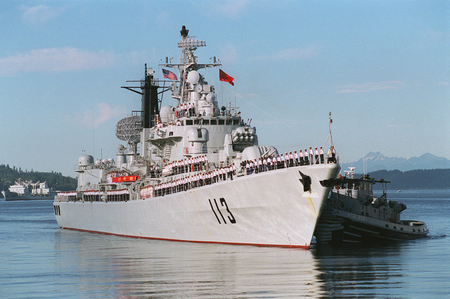 A starboard bow view of the Chinese Peoples Liberation Navy LUHU (TYPE 052) CLASS Destroyer QINGDAO (DDG 113) being assisted by a tugboat, while docking at Naval Station Everett, Washington (WA)