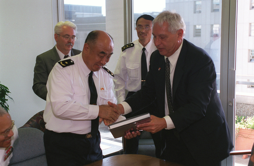 Chinese Peoples Liberation Navy Rear Admiral (RADM) Lu Fangqui (left), CHIEF of STAFF, North Sea Fleet, accepts a gift from the City of Seattle Mayor, Mr. Paul Schell, during a visit to the Mayor's office, part of the Chinese Peoples Liberation Navy, visit to Naval Station Everett, Washington (WA)