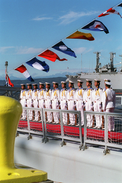 Chinese Peoples Liberation Navy Sailors stand at attention on the deck of the Chinese Peoples Liberation Navy LUHU (TYPE 052) CLASS Destroyer QINGDAO (DDG 113), during the Welcoming Ceremony for the Chinese Peoples Liberation Navy, held at Naval Station Everett, Washington (WA)
