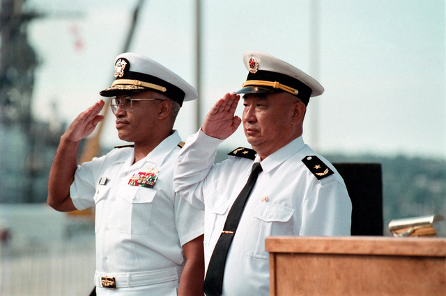 US Navy (USN) Rear Admiral (RADM) Vinson E. Smith (left), Commander, USN Region Northwest, and Chinese Peoples Liberation Navy Rear Admiral (RADM) Lu Fangqui (left), CHIEF of STAFF, North Sea Fleet, render salutes during the Welcoming Ceremony for the Chinese Peoples Liberation Navys, visit to Naval Station Everett, Washington (WA)