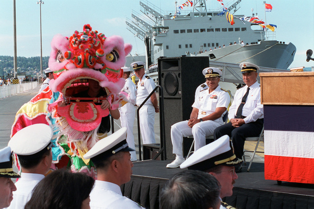 US Navy (USN) Rear Admiral (RADM) Vinson E. Smith (seated left on podium), Commander, USN Region Northwest, and Chinese Peoples Liberation Navy RADM Lu Fangqui, CHIEF of STAFF, North Sea Fleet, enjoy the festivities, during the Welcoming Ceremony for the Chinese Peoples Liberation Navy, held at Naval Station Everett, Washington (WA)