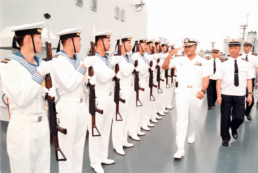 A Chinese Peoples Liberation Navy Honor Guard Team presents arms with their 7.62mm Type 81 assault rifles, as US Navy (USN) RADM Vinson E. Smith, Commander, USN Region Northwest, is piped onboard the Chinese Peoples Liberation Navy LUHU (TYPE 052) CLASS Destroyer QINGDAO (DDG 113), at Naval Station Everett, Washington (WA)