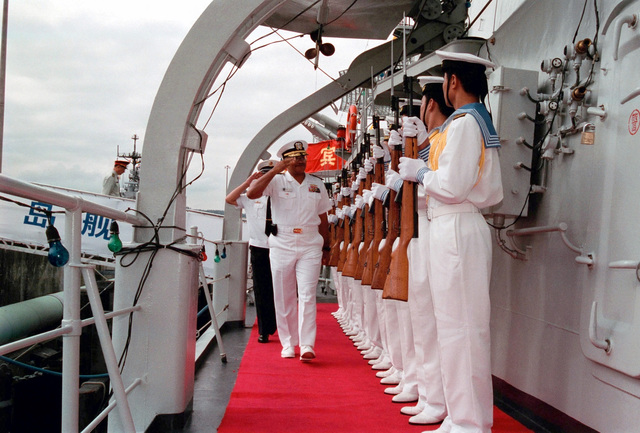 A Chinese Peoples Liberation Navy Honor Guard Team presents arms with their 7.62mm Type 68 assault rifles, as US Navy (USN) RADM Vinson E. Smith, Commander, USN Region Northwest, is piped onboard the Chinese Peoples Liberation Navy LUHU (TYPE 052) CLASS Destroyer QINGDAO (DDG 113), at Naval Station Everett, Washington (WA)