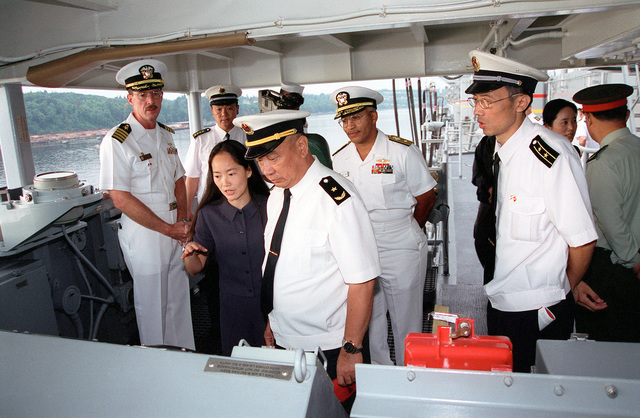 A Female Chinese Interpreter translates information to Chinese Peoples Liberation Navy Rear Admiral (RADM) Lu Fangqui, CHIEF of STAFF, North Sea Flee, during a tour onboard the Fast Combat Support Ship USS BRIDGE (AOE 10). US Navy (USN) Captain (CAPT) Richard B. Wren, Commanding Officer, USS BRIDGE, and US Navy (USN) RADM Vinson E. Smith, Commander, USN Region Northwest, stand in the background