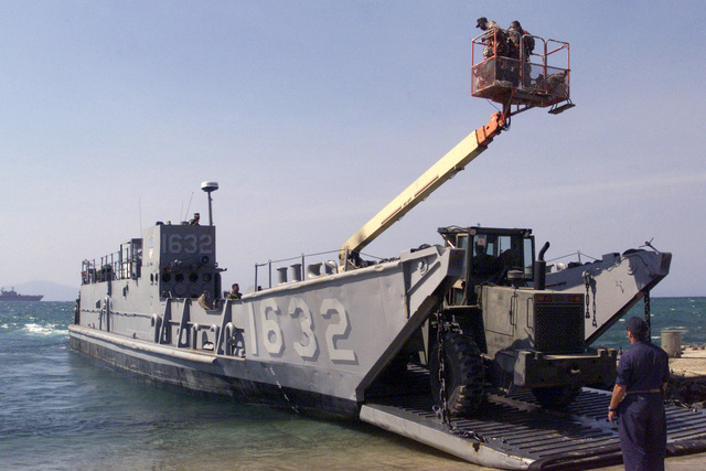 A Marine from MEU Service Support Group 13, 13th Marine Expeditionary Unit (Special Operations Capable) (13th MEU(SOC)), pushes a Manlift Vehicle with a John Deere 644E TRAM onto a Landing Craft, Utility (LCU) in preparation for backload onto the USS Tarawa (LHA 1) during a Humanitarian Assistance Operation in East Timor. Marines and sailors from Tarawa Amphibious Ready Group spent three days in East Timor providing Medical and Community Relations Services to help rebuild the war torn nation