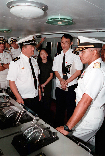 Chinese Peoples Liberation Navy Captain (CAPT) Fu Guosen (foreground left), Commanding Officer of the LUHU (TYPE 052) CLASS Destroyer QINGDAO (DDG 113), briefs US Navy (USN) RADM Vinson E. Smith, Commander, USN Region Northwest, during a tour his ship. An unidentified Chinese Peoples Liberation Navy Lieutenant (LT), a female Chinese Interpreter, and other USN Officers, look on