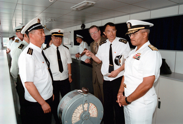 US Navy (USN) RADM Vinson E. Smith (right), Commander, USN Region Northwest, is given a tour of the bridge onboard the Chinese Peoples Liberation Navy LUHU (TYPE 052) CLASS Destroyer QINGDAO (DDG 113). Chinese Peoples Liberation Navy Rear Admiral (RADM) Lu Fangqui (center), CHIEF of STAFF, North Sea Fleet, and Chinese Peoples Liberation Navy Captain (CAPT) Fu Guosen look on