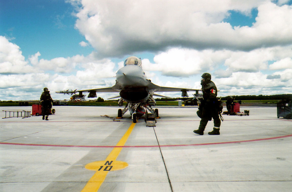 Maintenance personnel from the 174th Tactical Fighter Wing, New York Air National Guard, wear Mission-Oriented Protective Posture response level 4 (MOPP-4) gear as they perform a preflight inspection on an F-16 Fighting Falcon aircraft parked on the Flight line