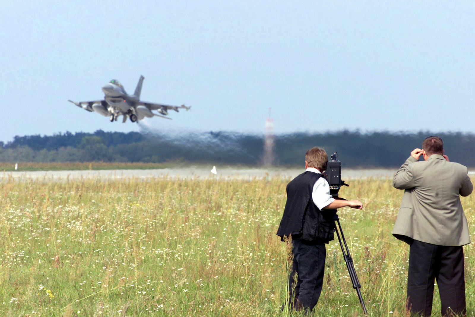 Members of a Slovakian news agency film an F-16 Fighting Falcon aircraft from the 510th Fighter Squadron, Aviano Air Base, Italy, as it lifts-off from Kuchyna Air Base, Slovakia, on September 18, 2000 in support of Exercise IRON CLAW
